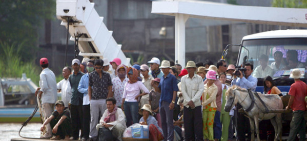 This packed ferry crossing the Mekong River in Cambodia highlights robust economic growth in ASEAN.
